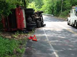 A witness said the truck was going around a bend when a tire blew out, causing it to overturn.