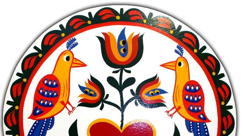 """Two distlefinks, a German word meaning """"thistle finch"""" or goldfinch birds, are the focus of this Eric Claypoole design. The birds are said to represent good luck. The heart represents love and the tulip represents faith. """"Willkom"""" means """"welcome to our home."""""""