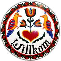 "Two distlefinks, a German word meaning ""thistle finch"" or goldfinch birds, are the focus of this Eric Claypoole design. The birds are said to represent good luck. The heart represents love and the tulip represents faith. ""Willkom"" means ""welcome to our home."""