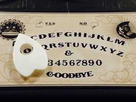 A collection of Ouija boards are on display that span decades.