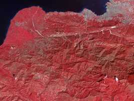 The ASTER instrument on NASA's Terra spacecraft captured this false-color image of Haiti on Jan. 21, 2010, nine days after a magnitude 7.0 earthquake struck the region and caused massive damage and loss of life, and one day after a large 5.9 aftershock caused additional damage. Tiny dots of white against the plant-covered landscape (red in this image) are possible landslides, a common occurrence in mountainous terrain after large earthquakes. The possible landslides were identified by carefully comparing the new image with an image acquired one year ago.