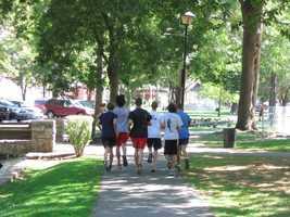 High school students jog through Lititz Springs Park.