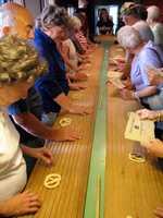 Tourists make pretzels during a tour of the Julius Sturgis Pretzel Factory.