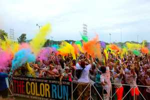 "Runners gather at the stage to take part in ""the color drop"" to illuminate the madness of the 5K"