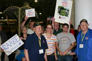 Two brothers, one a WWII vet and the other a Korean War vet, find their family in the crowd.