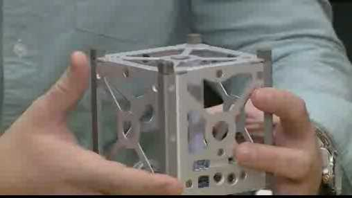 student holds CubeSat