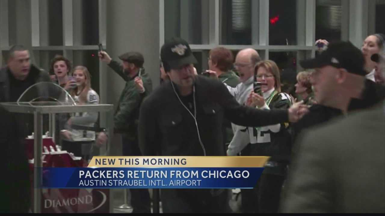 Fans gathered at Green Bay's airport to welcome home the Green Bay Packers, who clinched a playoff spot and division championship with Sunday's win over the Chicago Bears.