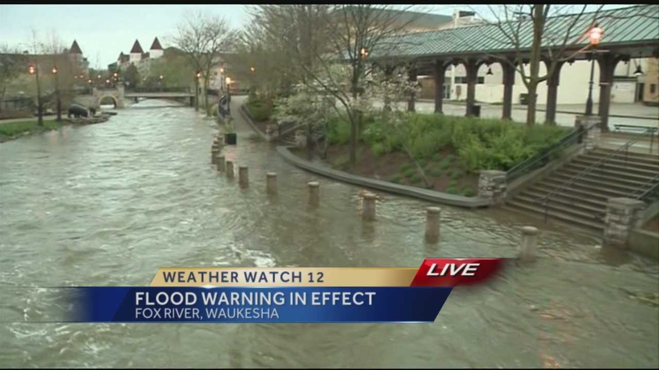 Heavy Monday rains have sent the Fox River in Waukesha over its banks, flooding walkways near the Love Bridge.
