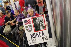 Family, friends and strangers gathered at Mitchell Airport to greet the vets that took a one day trip to Washington D.C. to see the memorials built in their honor.