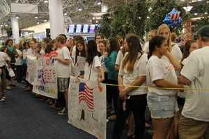 Thousands of family, friend and strangers gather in the main terminal of the airport.