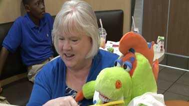 woman brushing stuffed animals's teeth