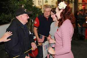 The Bombshells talk with a vet who had already taken his Honor Flight and returned to the airport to welcome home other vets.