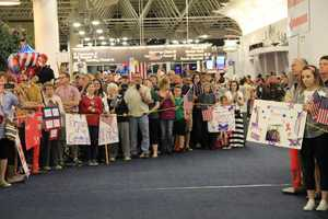 After a whirlwind trip the vets return to Mitchell Airport to thousands of cheering friends, family and well wishers.