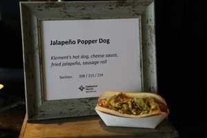 The Jalapeno Popper Dog starts with a Klement's hot dog and is topped with cheese sauce and fried jalapenos on a sausage roll.
