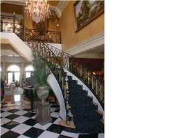 Marble granite two story foyer with custom iron spiral staircase.