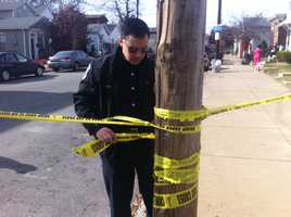 An officer ties crime scene tape to keep the scene safe
