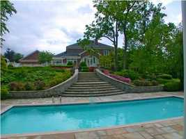 Behind the home, a path leads down to a beautiful pool.