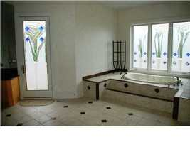 Gorgeous spa tub sits below custom stain-glass windows.