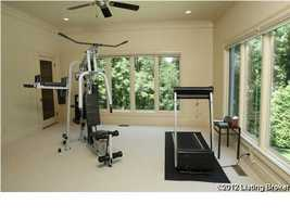 Steps from the master bedroom is a workout room that includes a dry sauna and flat screen overlooking this wooded retreat.