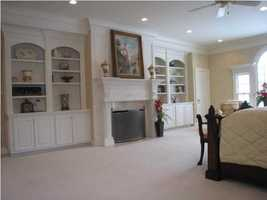The master bedroom also custom shelving units and its own fireplace.