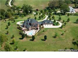 Aerial view from the back of the home, allows you to truly see the expansive pool area. Also, shows the 4 car garage.
