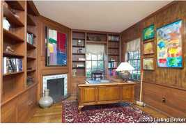 Study room with a colorful art piece above the fireplace.