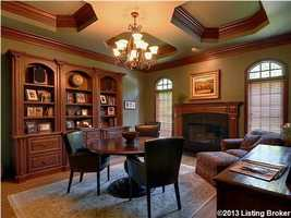 Personal office is quite spacious and features a custom wooden bookcase, desk, and mouldings.