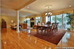 The open floor plan features beautiful columns, vaulted ceilings, and recessed lighting.