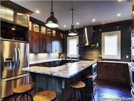The kitchen has stainless steel appliances, granite counter tops, and custom cabinetry.