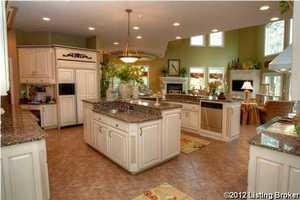 A gourmet kitchen with two islands, double ovens, and double dishwashers.
