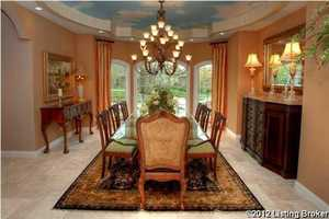 A formal dining room with trayed ceiling.