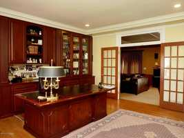 The office features a built-in cherry wood unit and desk.