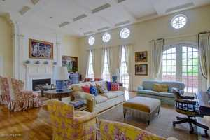 The formal living room is well lit, quite spacious, and boasts beautiful hardwood floors.