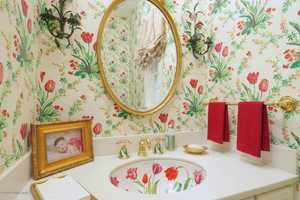 This half bathroom features a hand painted sink. There are 2 half bathrooms and 7 full bathrooms in the home.