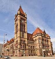 "City Hall, ""a large red bulding in a Romanesque style, with a lofty tower, erected at a cost of $1,600,000."""
