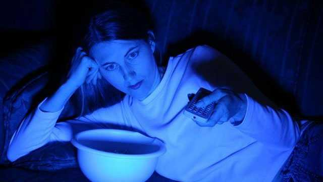 woman with remote watching TV in the dark