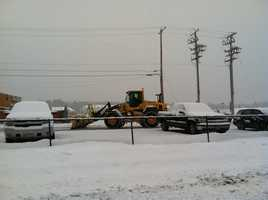 Crews work to keep the parking lot at Cabelas in Scarborough clear of snow.