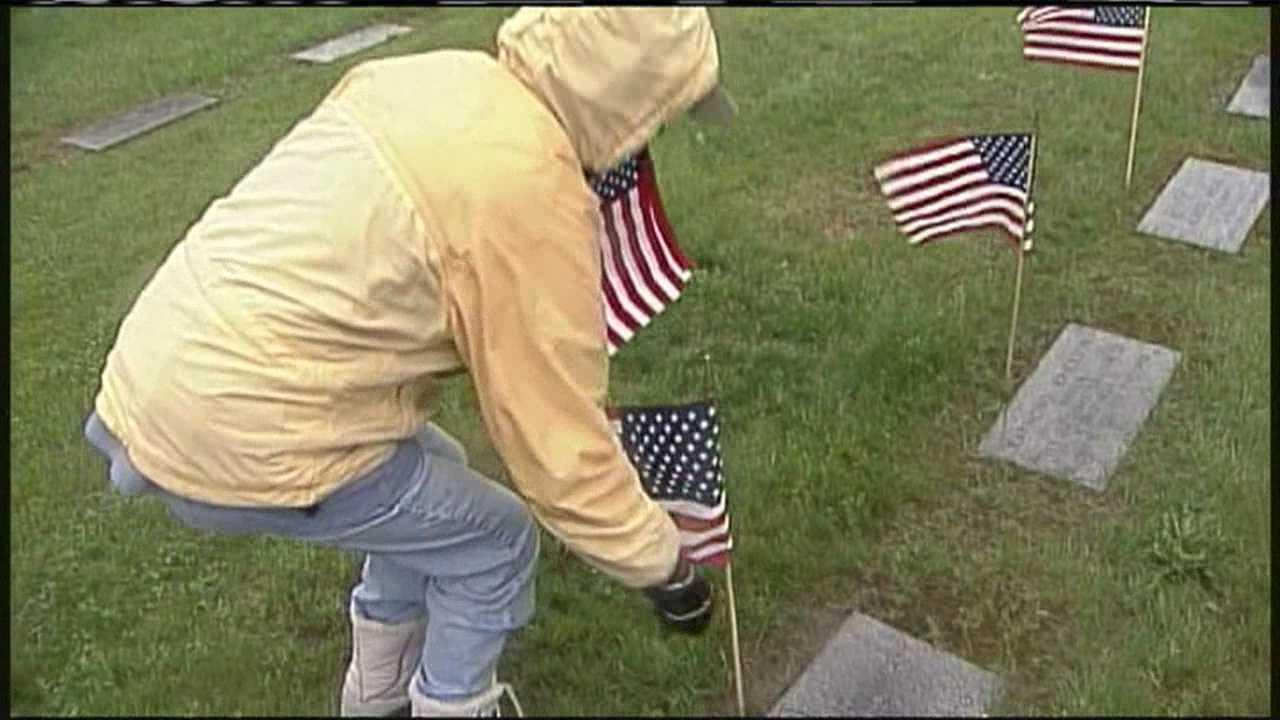 Volunteers place flags on veterans' graves