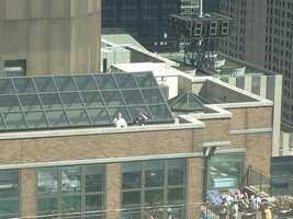People in neighboring buildings look on rescue efforts get underway.