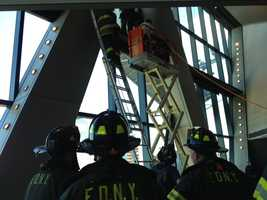 Firefighters worked to cut a hole into a window to get at the stranded workers.