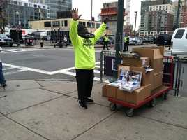 A man hands out World Series guides on the street.
