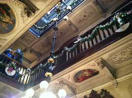 Balustrades on the staircases inside the Victoria Mansion in Portland are decorated with boughs and lights.