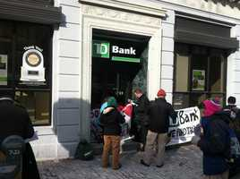 Two protesters chained themselves to the door of the TD Bank on Congress Street in Portland on Wednesday.