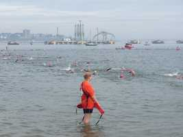 One of the hundreds of volunteers keeps a sharp eye on racers as they compete in the swimming leg of the Tri for a Cure in South Portland on Sunday.