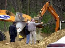 """State Police investigators examine dirt as a front end loader and an excavator dig for the bodies of victims of Bulger and Stephen """"The Rifleman"""" Flemmi in Hopkinton, Mass."""