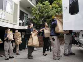 """FBI agents load evidence bags into a truck outside an apartment complex where James """"Whitey"""" Bulger and Catherine Greig were arrested."""