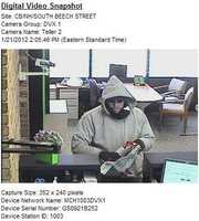 "Manchester Bank Robbery ((Press Release)) On Saturday January 21st 2012 just before 2 pm Officers and Detectives from the Manchester Police Department responded to the TD Bank on the corner of South Beech St and Cilley Rd regarding the report of a robbery. The suspect was described as being a white male, wearing jeans, sneakers, a grey sweatshirt, sunglasses, a black clothing item partially covering his face, possibly a black rimmed hat, and black gloves. This subject was also described as having a beard, in his mid-twenties being approximately six feet tall and having an average build - and to have been carrying an ""H&M"" shopping bag, which he eventually put the stolen money in. This suspect demanded money, however no weapons were seen - and he did say ""Thank You"" after obtaining the money. He fled the bank running Southerly South Beech St toward South Willow St, and made off with a significant quantity of money.  The incident is still under investigation, and the Manchester Police Department Detectives Division is requesting that should anyone have any information relating to this robbery that they call the Manchester Police Department at 668-871"
