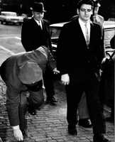 A guard handcuffed to Albert DeSalvo stoops to pick up a coin as they arrived at Middlesex Superior Court in Cambridge, Mass. for DeSalvo's trial on charges of assaulting four women in their suburban Boston homes, Jan. 12, 1967. DeSalvo claims to be the Boston Strangler but the charges are not related to the series of killings.
