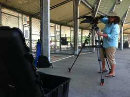 Camera crews set up the prompter near the batting cages.