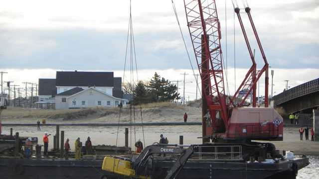 Crews used a crane to pull a 35,000-pound excavator from Hampton Harbor on Wednesday.